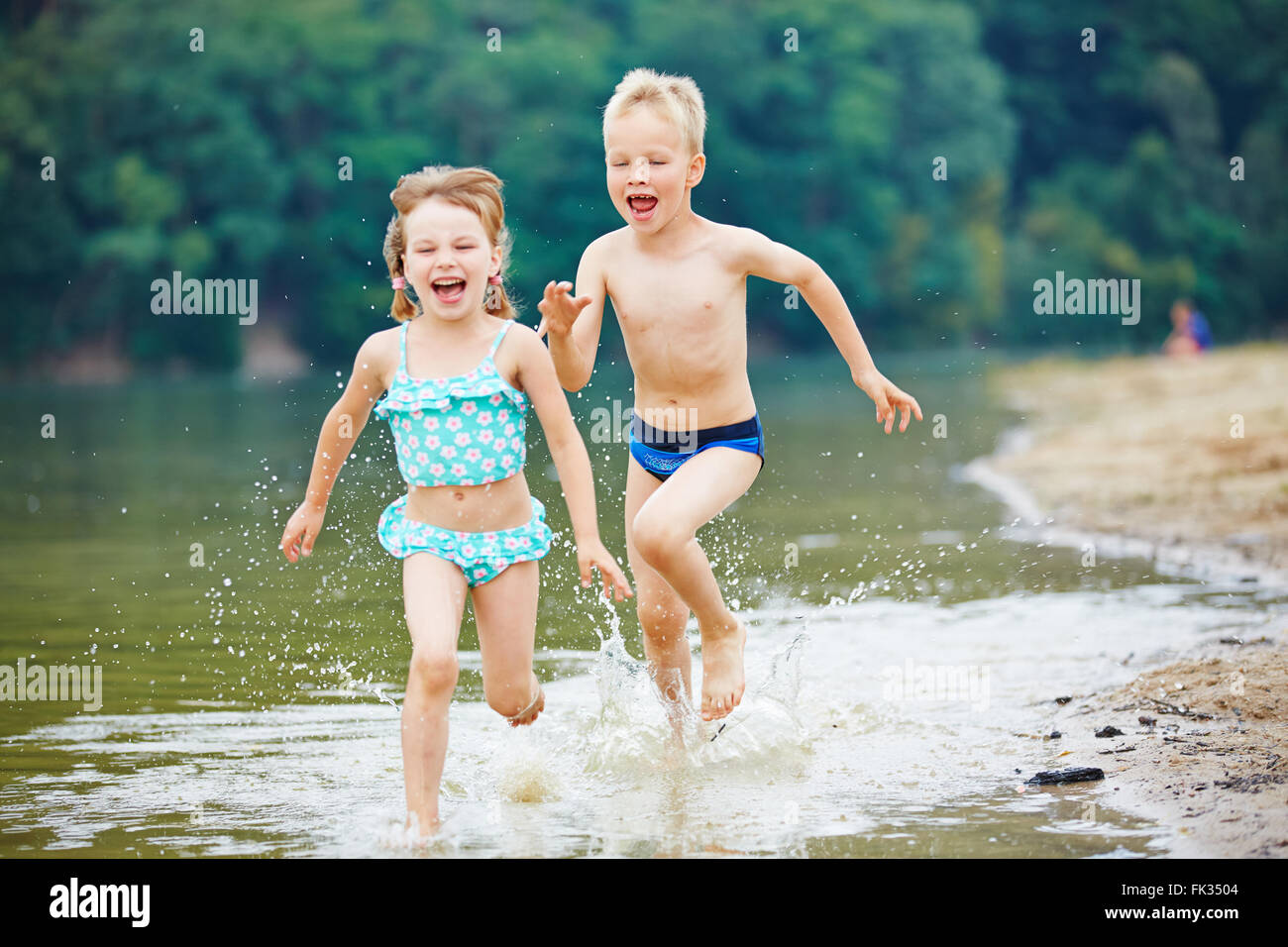 Two happy kids running through sea water in summer - Stock Image