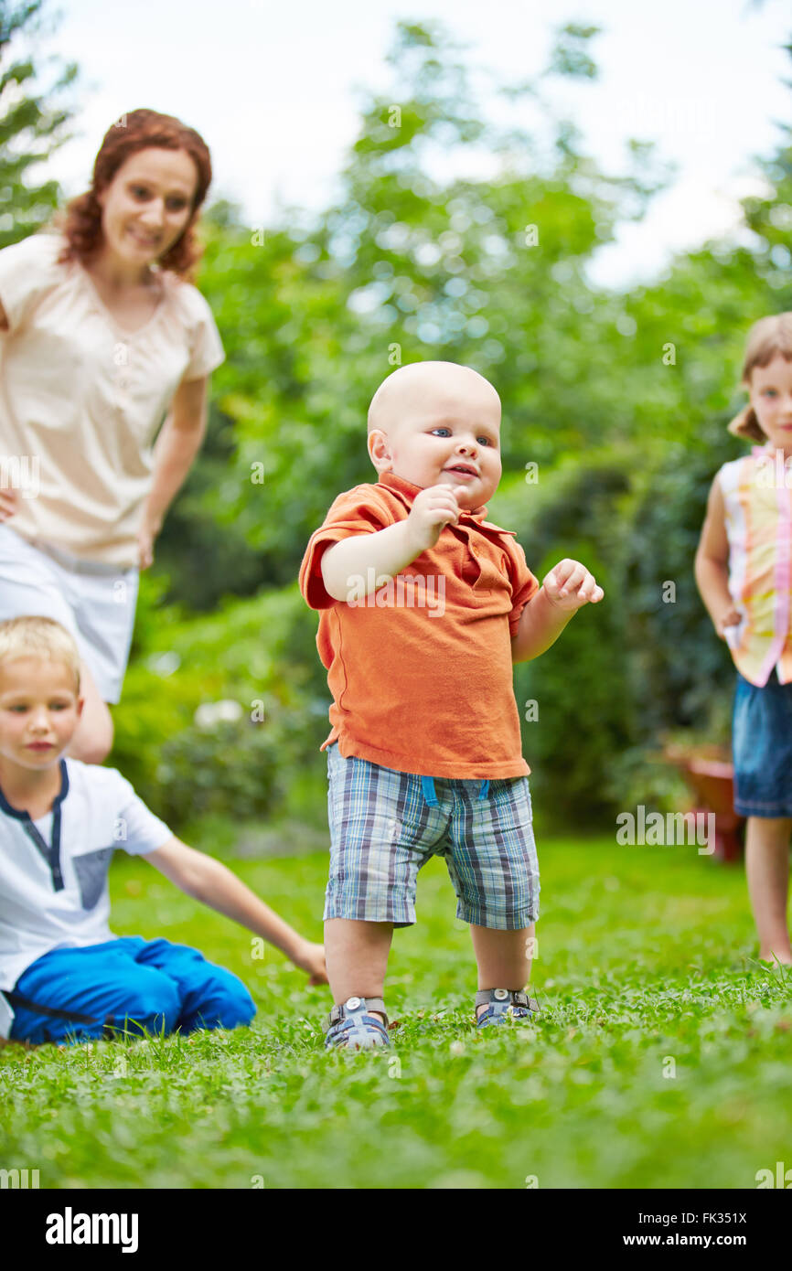 Proud baby learning first steps in garden in summer with family watching - Stock Image