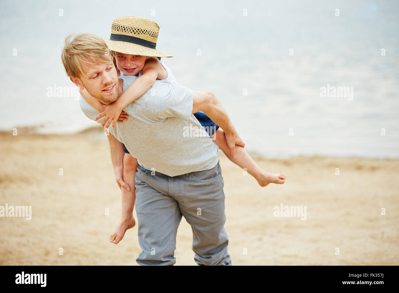 Man carrying girl piggyback on his back on a beach in summer - Stock Image
