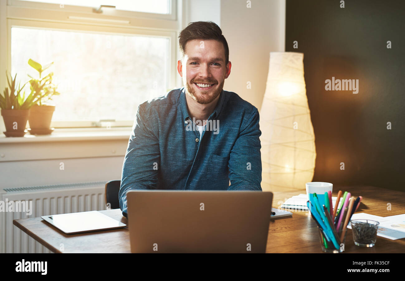 Entrepreneur at office with laptop looking at camera smiling - Stock Image