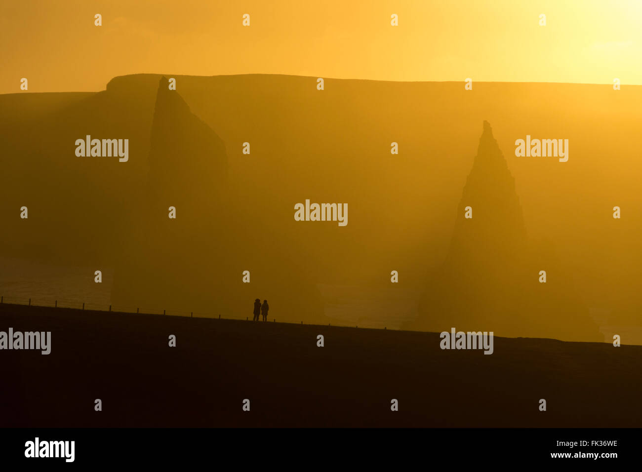 Two walkers looking at the Stacks of Duncansby on a very hazy day near sunset, Duncansby Head, Caithness, Scotland, Stock Photo