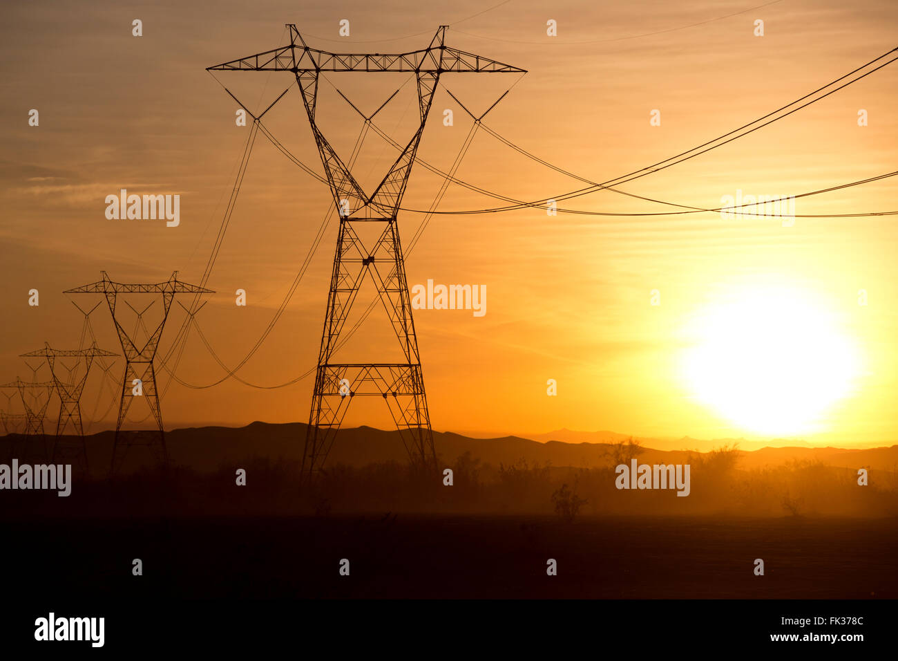 High tension power lines and the setting sun in the Sonoran Desert, California, USA - Stock Image