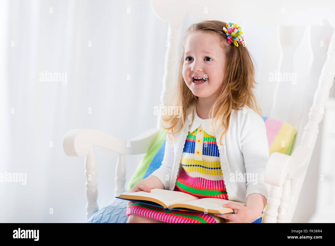Kids Read A Book. Children Reading Books In White Chair. Toddler Kid  Playing In White Bedroom. Preschooler Child Doing Homework.