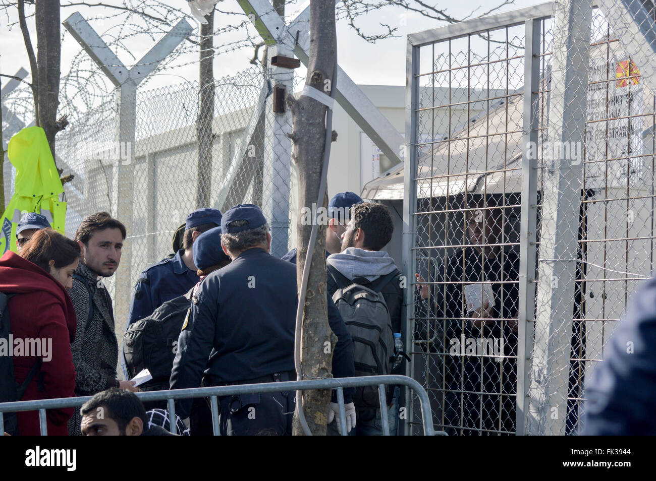 Police officers opened for a few minutes, the fence on Greece-Macedonia border and allow few refugees to cross. - Stock Image