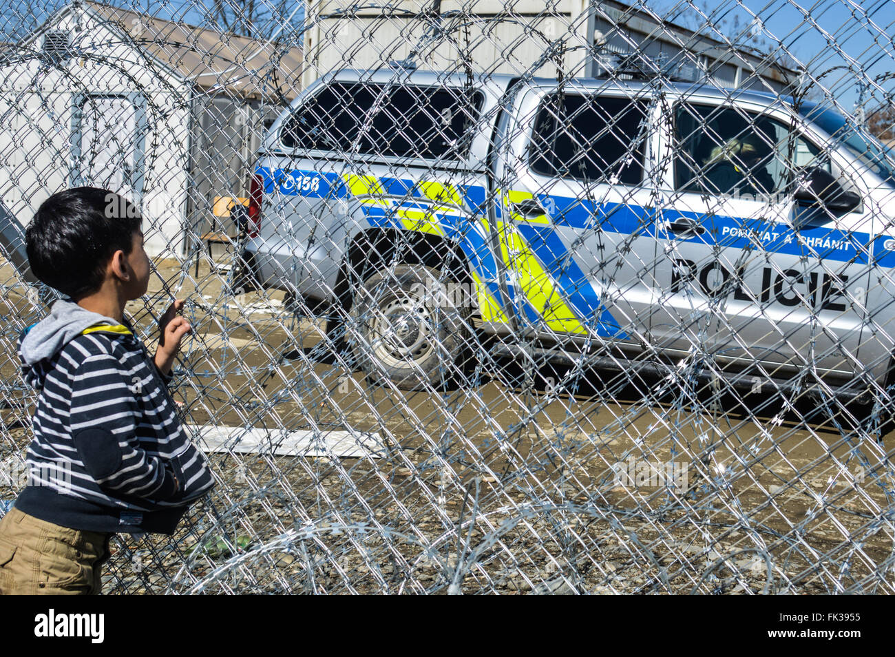 A child looking behind the fence on Greece-Macedonia border, near the village of Idomeni. - Stock Image