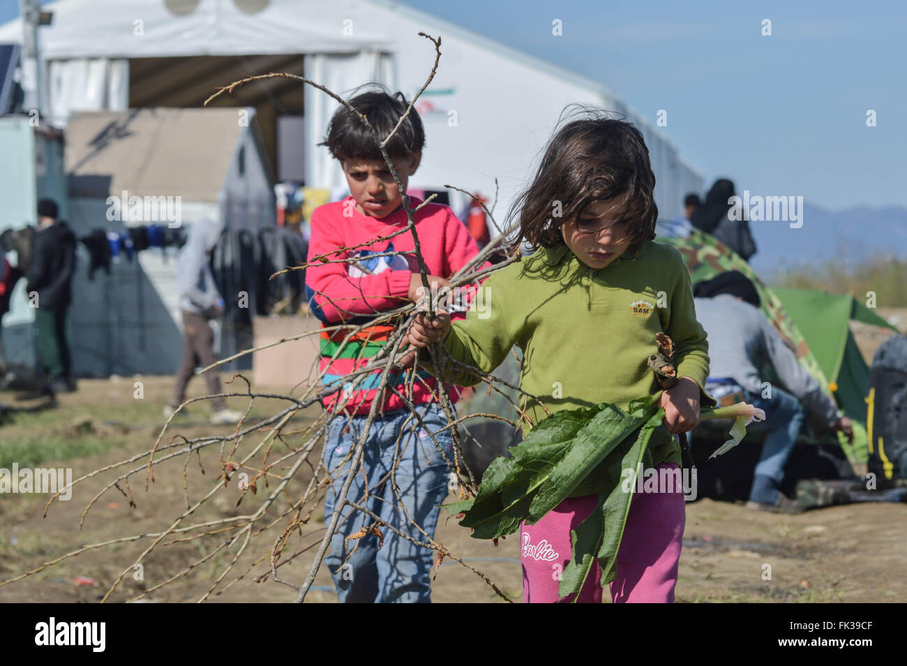 Two refugee children carry wood to light a fire to keep warm. - Stock Image