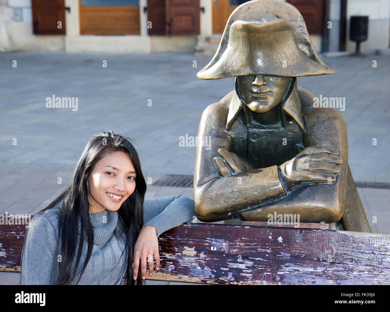 Asian tourist woman sitting on bench with Napoleon soldier at the Main square, Bratislava, Slovakia Stock Photo
