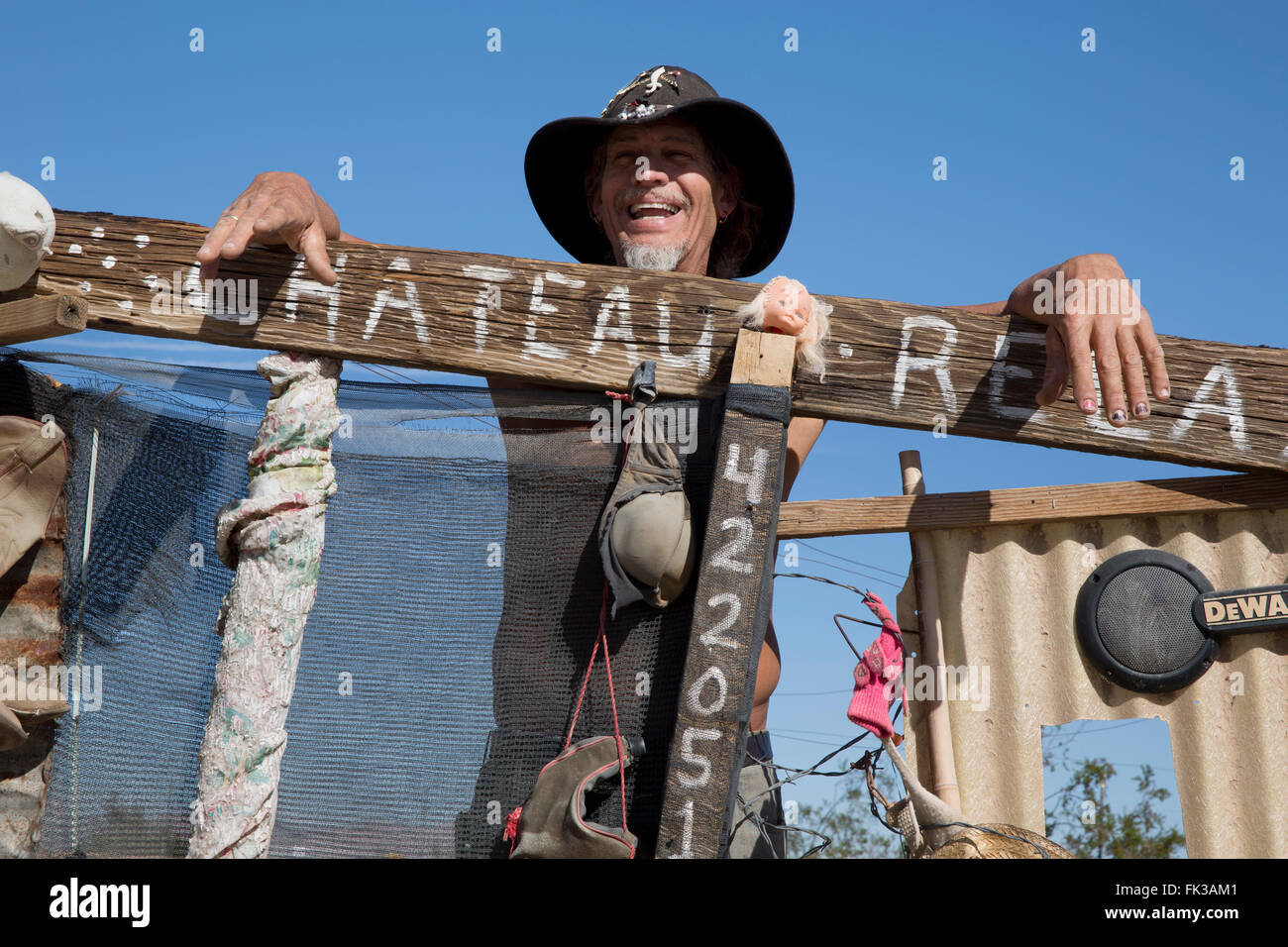 Karibe, a resident of Slab City, stands at the gate to his encampment, Niland, California USA - Stock Image