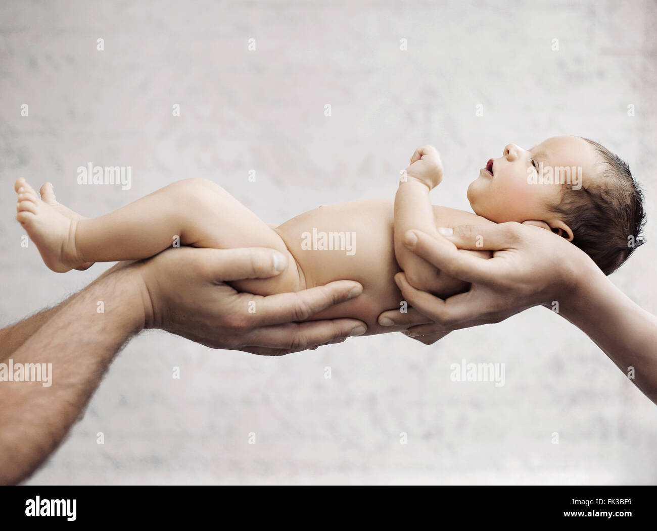 Newborn child sleeping on parents hand - Stock Image