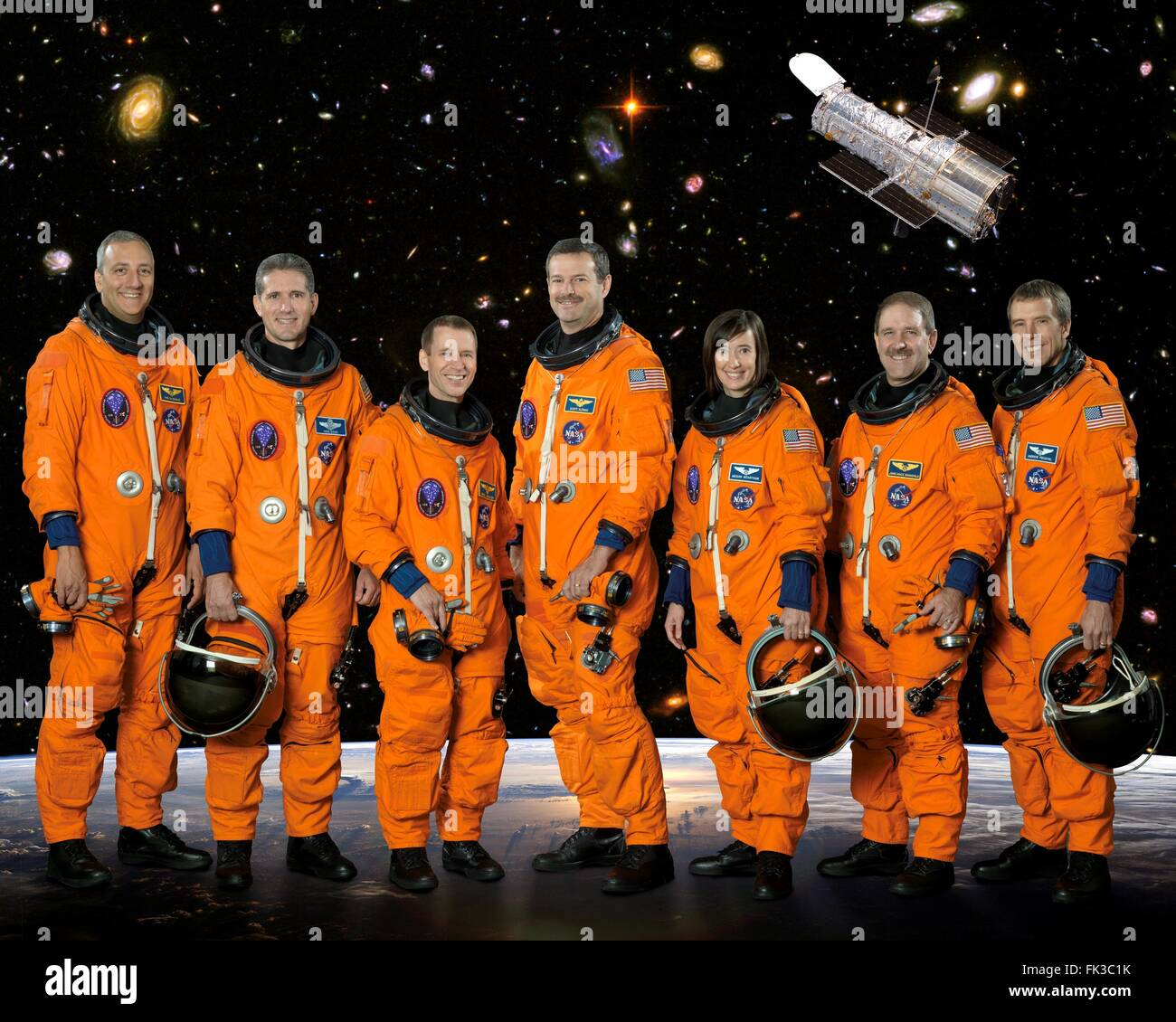 Group portrait of the STS-125 space shuttle crew astronauts in orange launch and entry suits at the Johnson Space - Stock Image