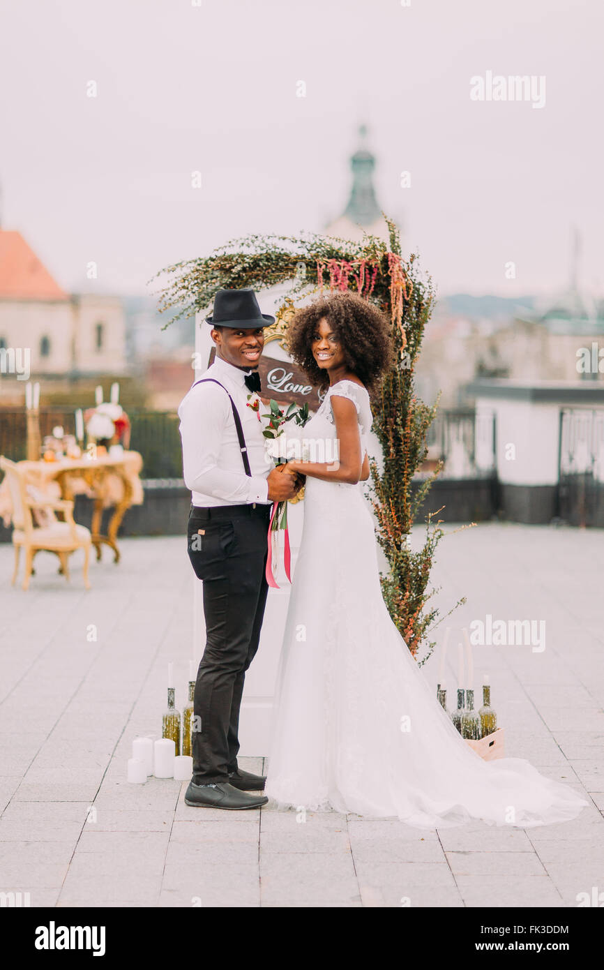Happy african bride and groom posing for camera smiling on the rooftop - Stock Image