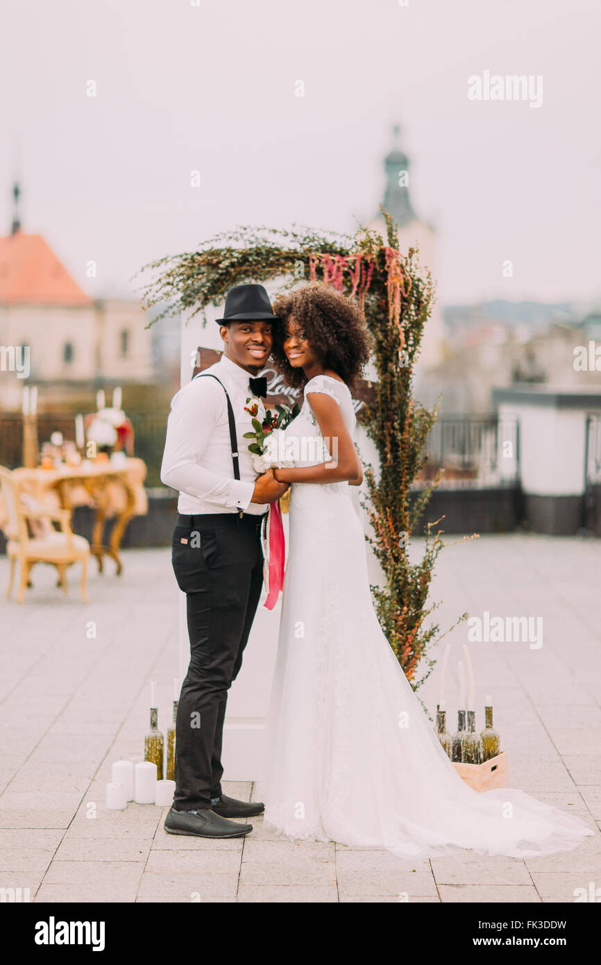Black wedding couple posing for camera on the rooftop and smiling - Stock Image