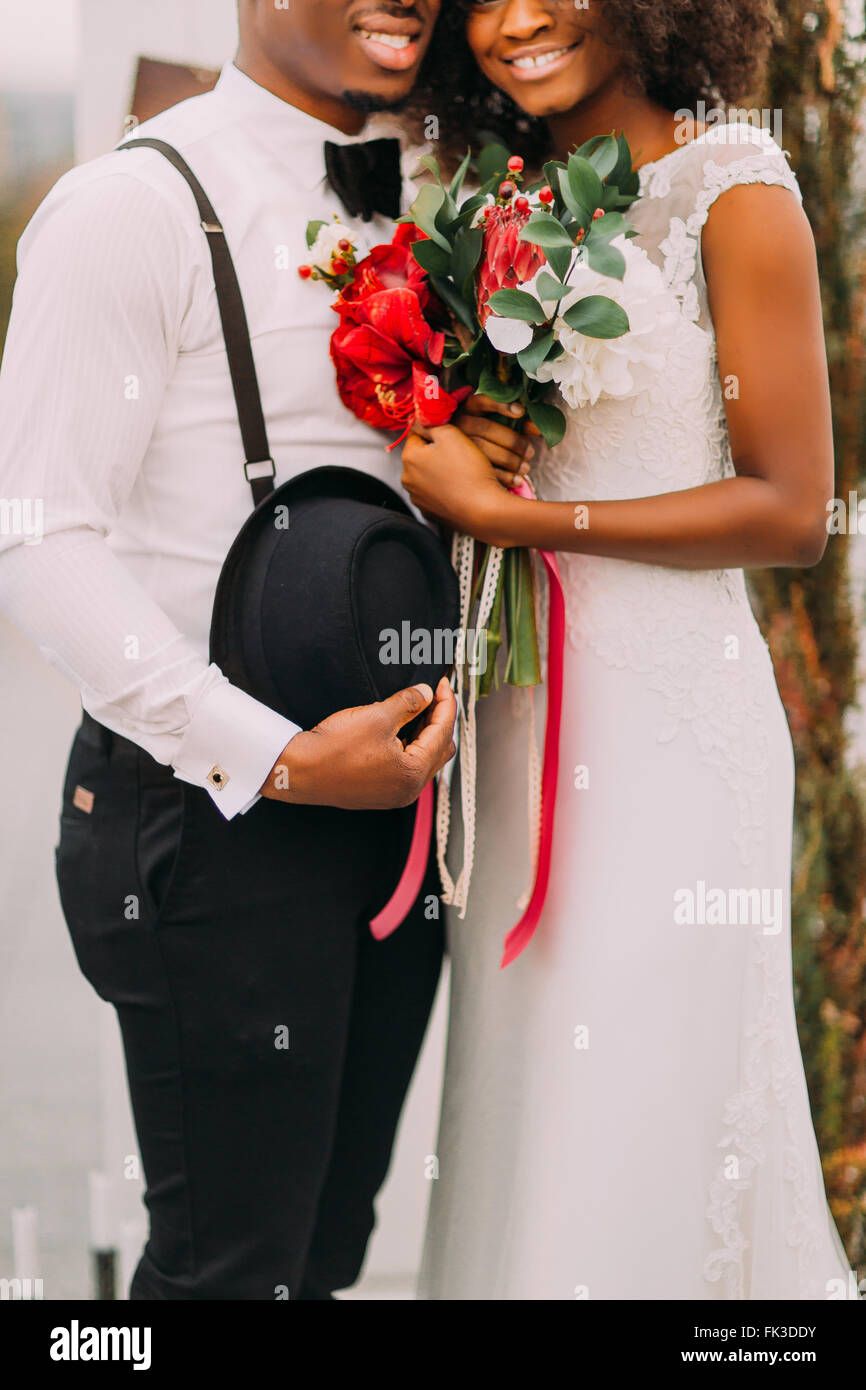 Young pretty black bride and groom happily smiling and holding a bouquet in half length - Stock Image