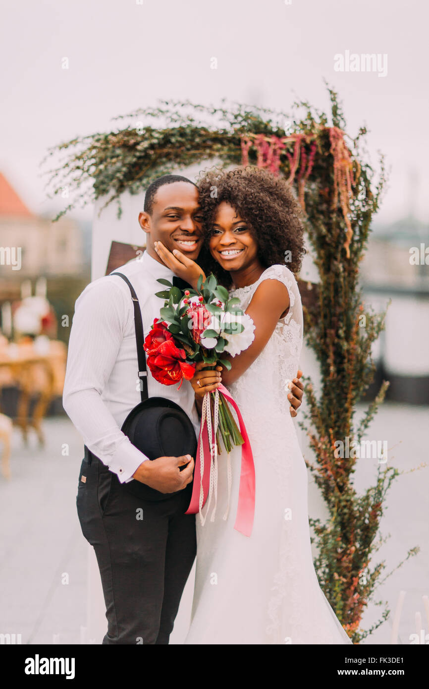 Happy black newlyweds smiling and hugging on the rooftop during their wedding ceremony - Stock Image