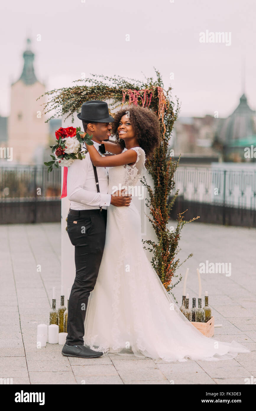 Beautiful young black wedding couple dreamily looks into the sky - Stock Image