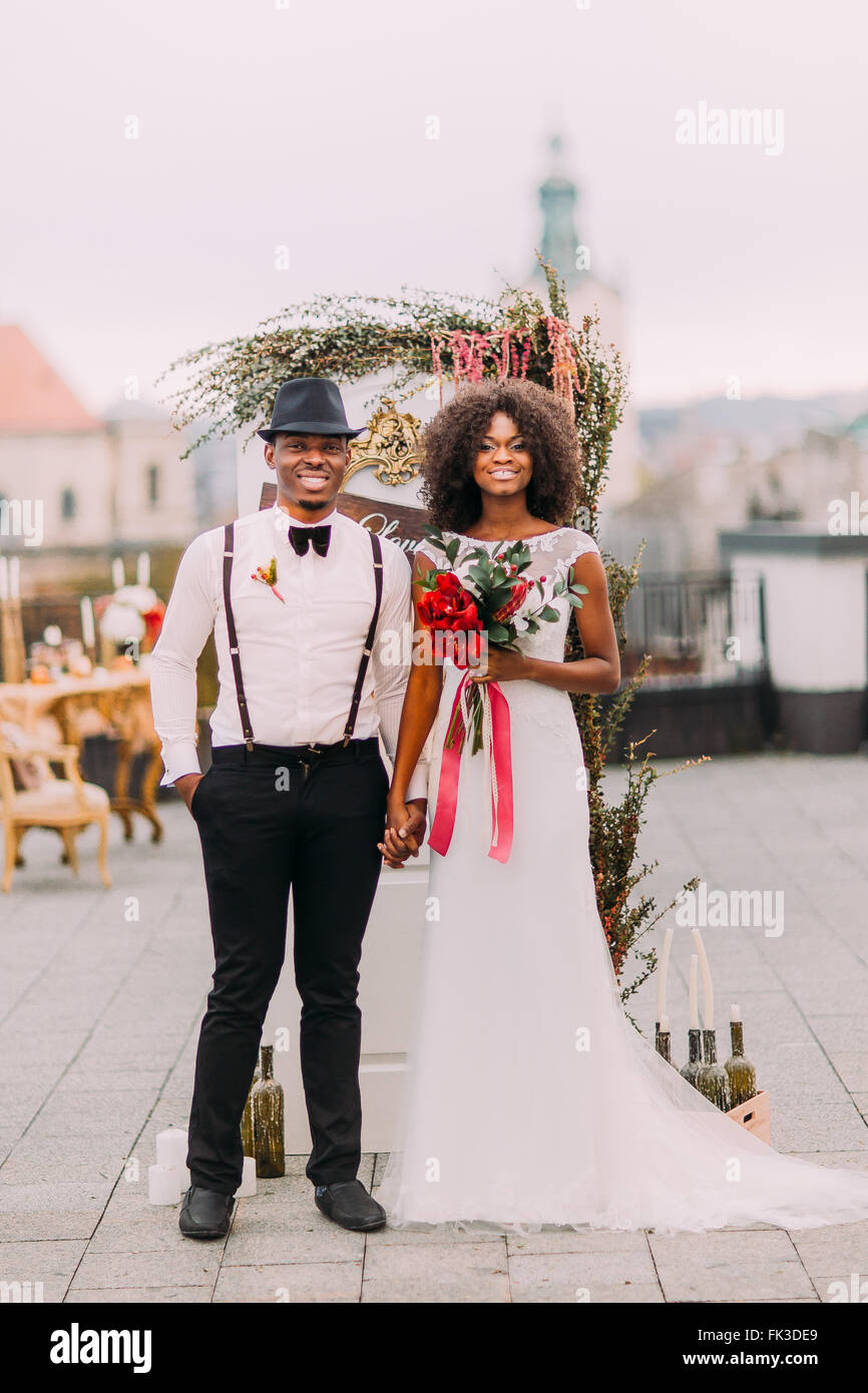 Cheerful african newlyweds holding hands and smiling at the wedding ceremony on the rooftop - Stock Image