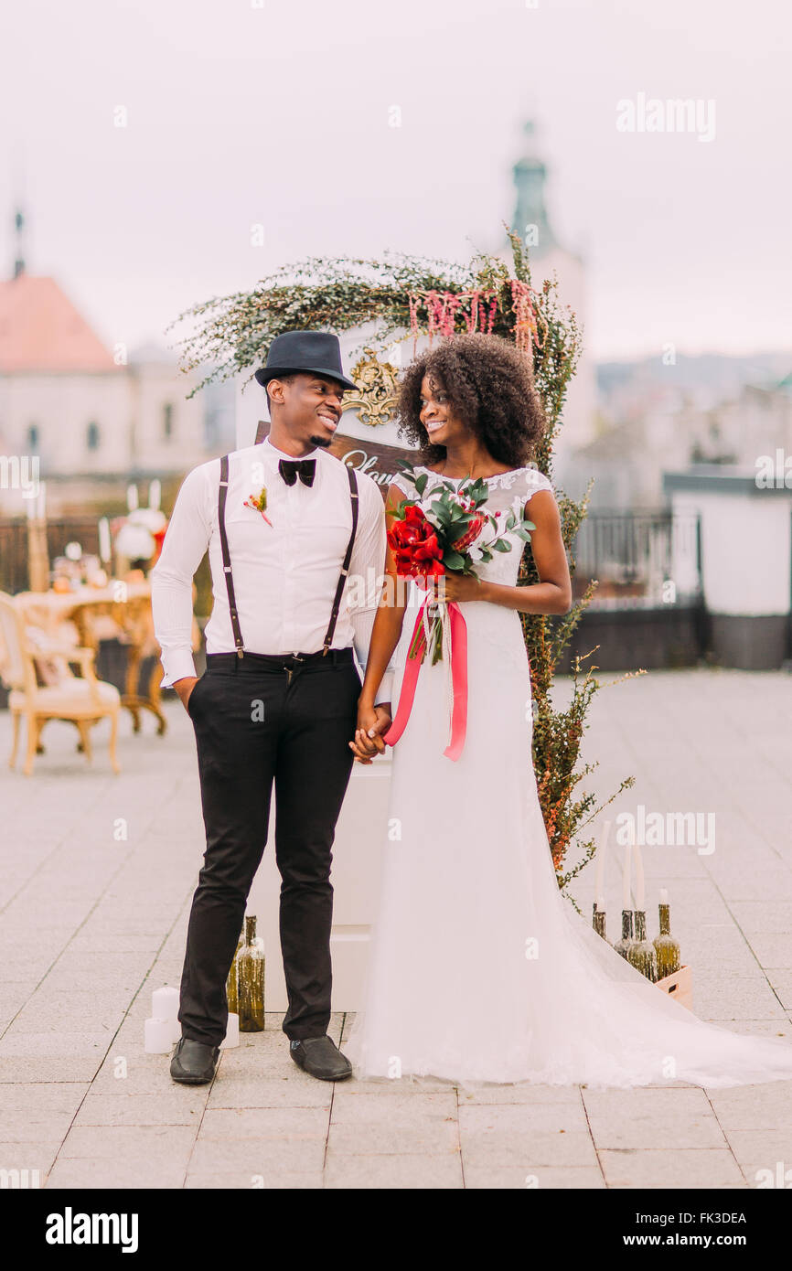 Charming african newlyweds dreamily looks on each other. Wedding day. Rooftop. Lviv architecture on background - Stock Image