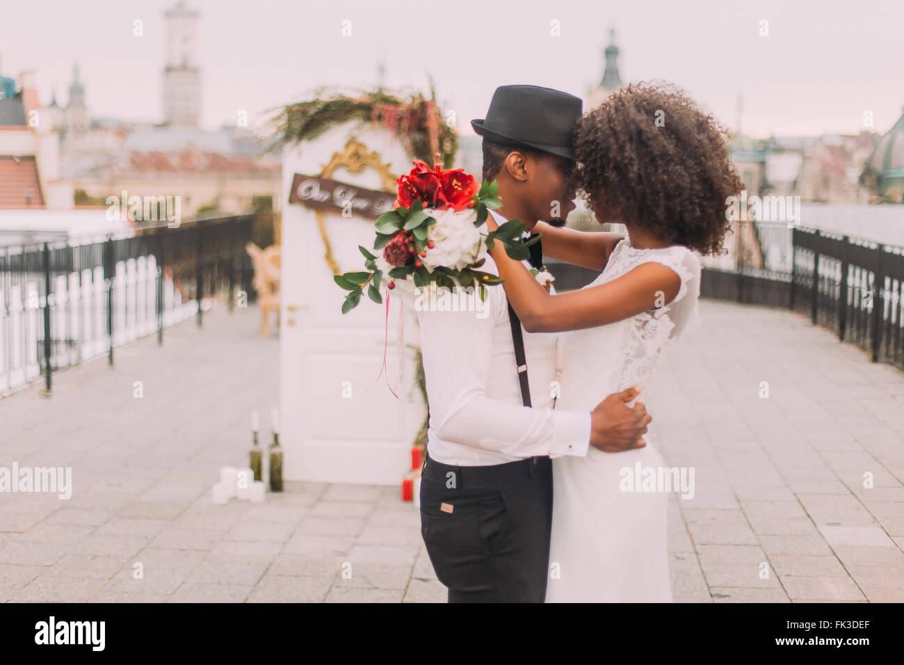 Happy black wedding couple softly hugging on the rooftop during the wedding ceremony - Stock Image