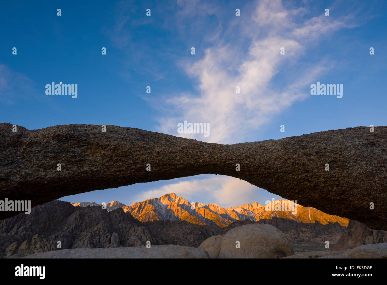 Mt. Whitney Mt. Muir and Mt. Irvine hit by the alpine glow of the rising sun as seen through the Lathe Arch in the - Stock Image