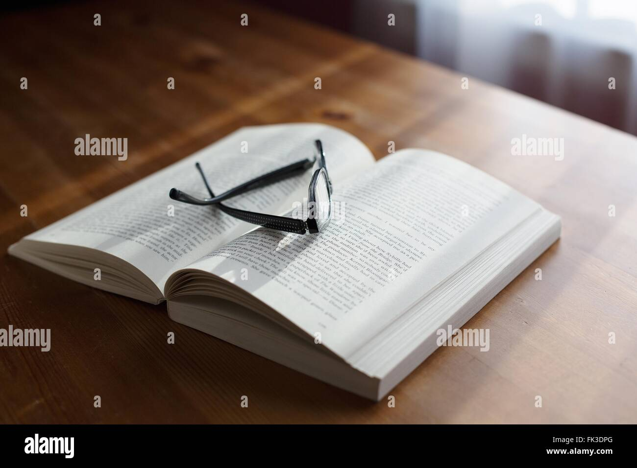 A pair of glasses on top of a book. Stock Photo