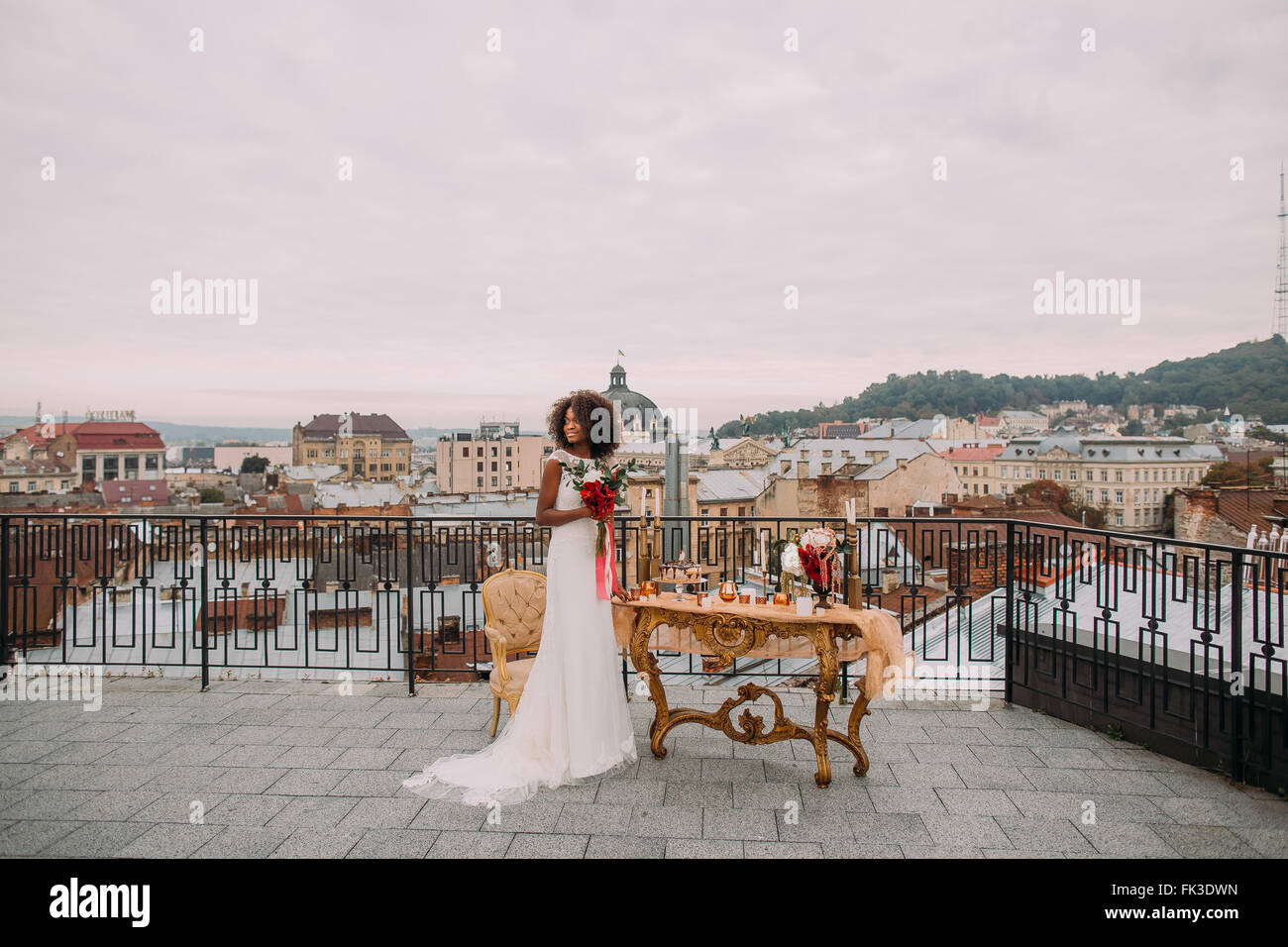 Pretty african bride with wedding bouquet in hands standing on the terrace - Stock Image