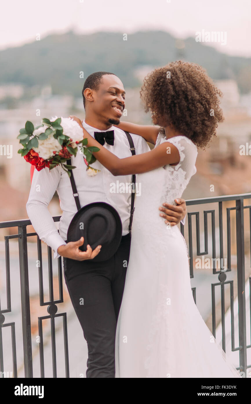 Happy african bride and groom softly hugging - Stock Image