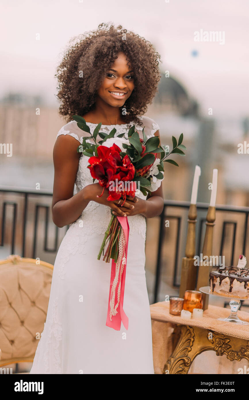 African bride cheerfully smiling with bouquet of red flowers in hands - Stock Image