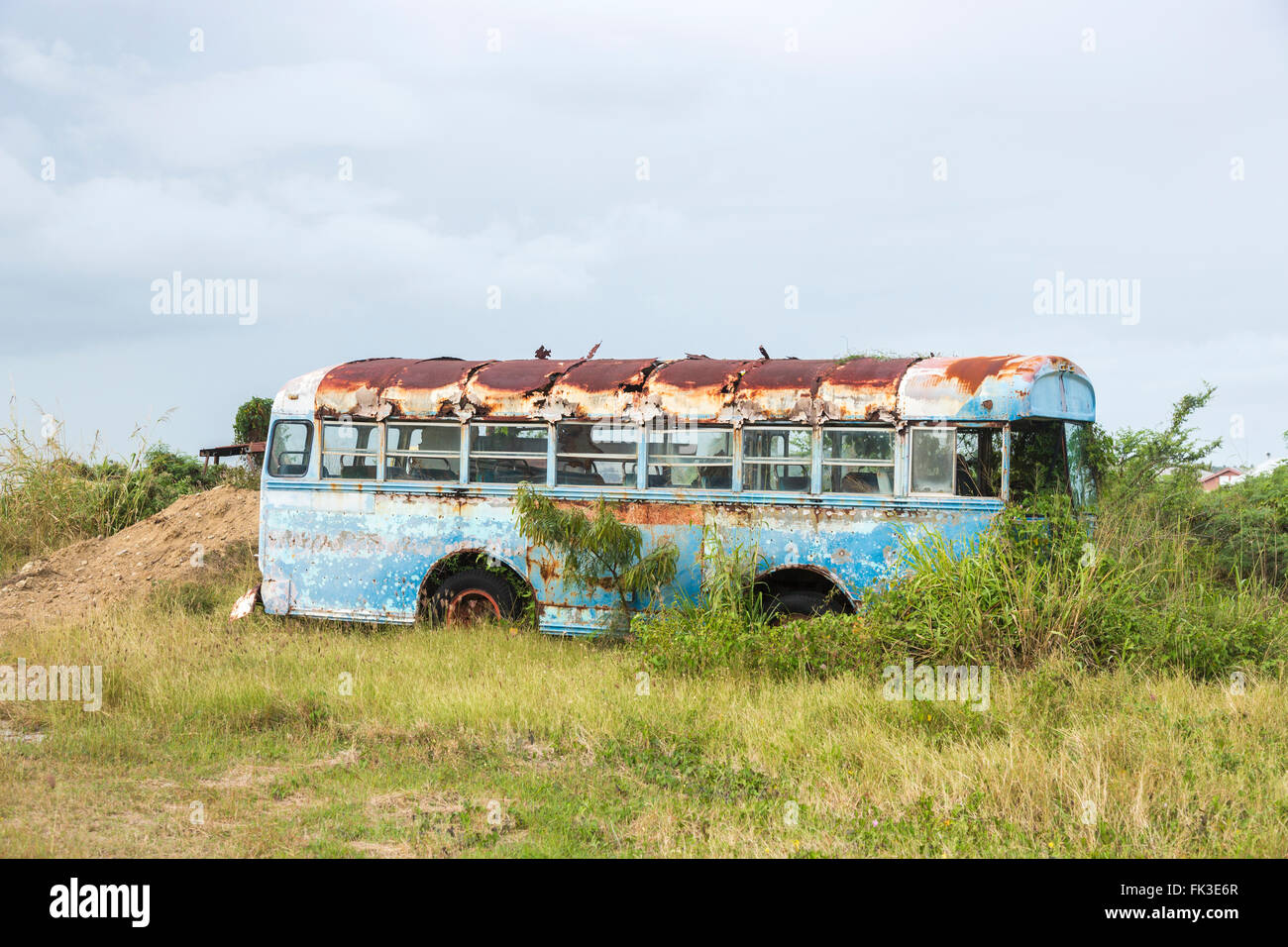 Decaying Blue Bird coach in Ogg Spencer's Trucking scrapyard, Liberta, south Antigua, Antigua and Barbuda, West - Stock Image