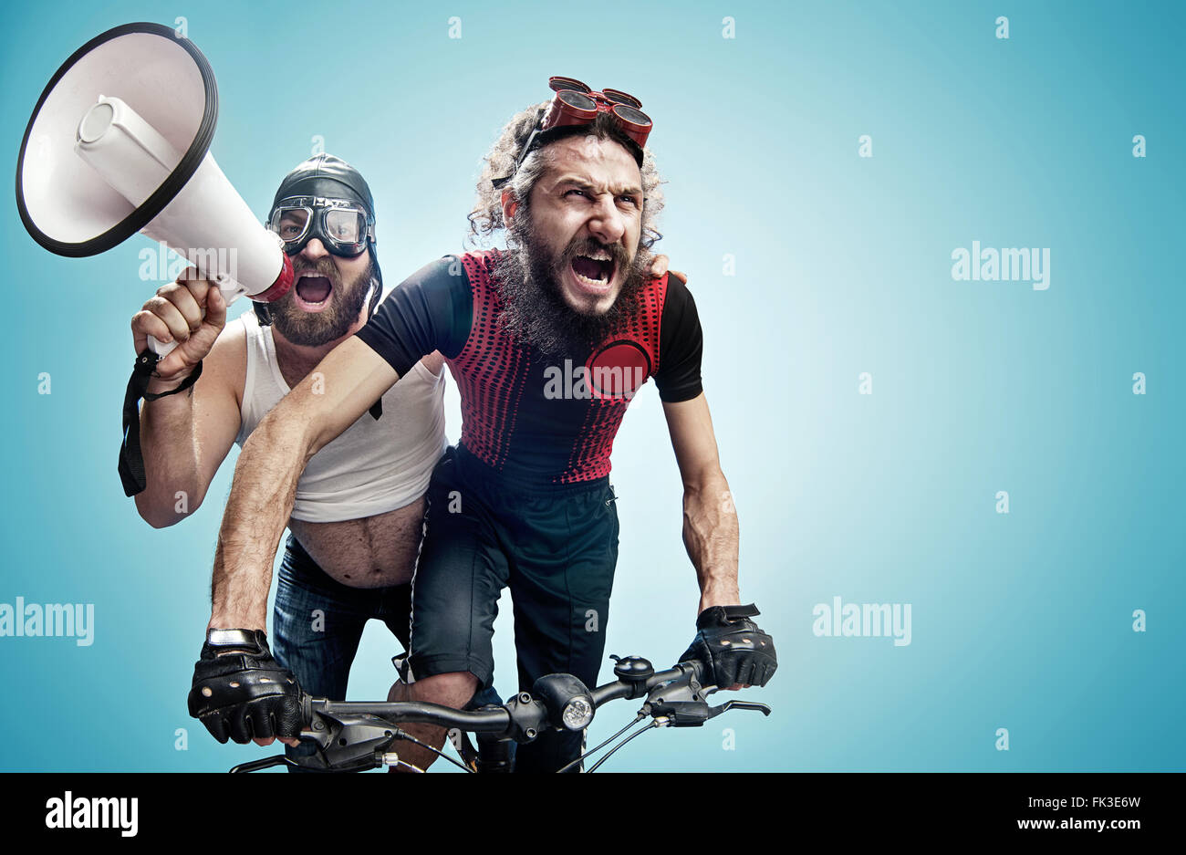 Two hilarious bicyclists involved in a contest - Stock Image