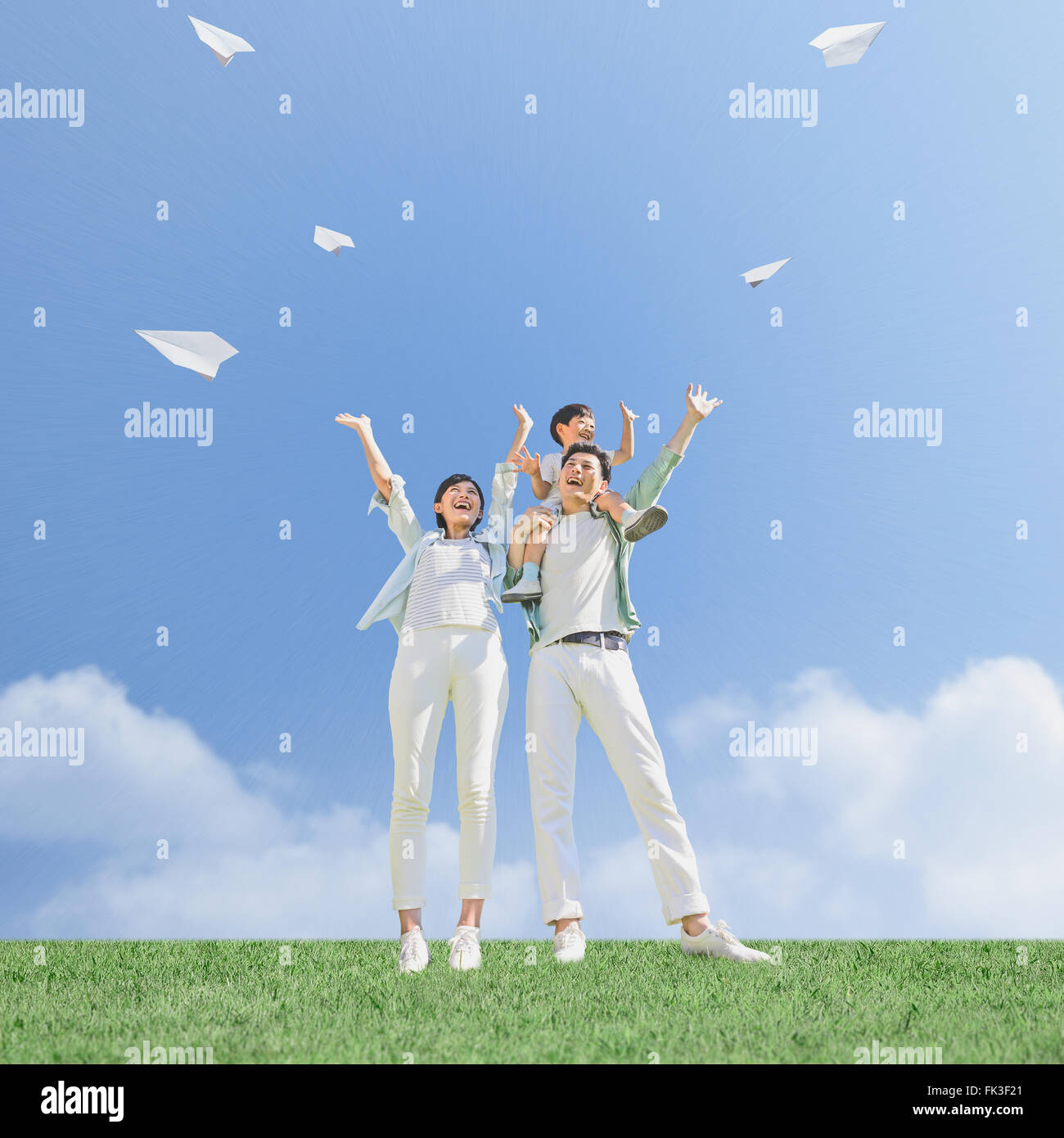 Japanese family flying paper planes in a city park Stock Photo