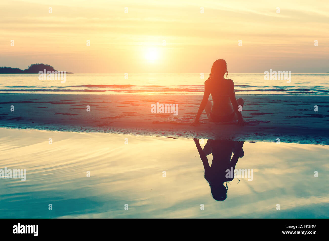 Young woman sitting on the beach, silhouette at sunset. - Stock Image