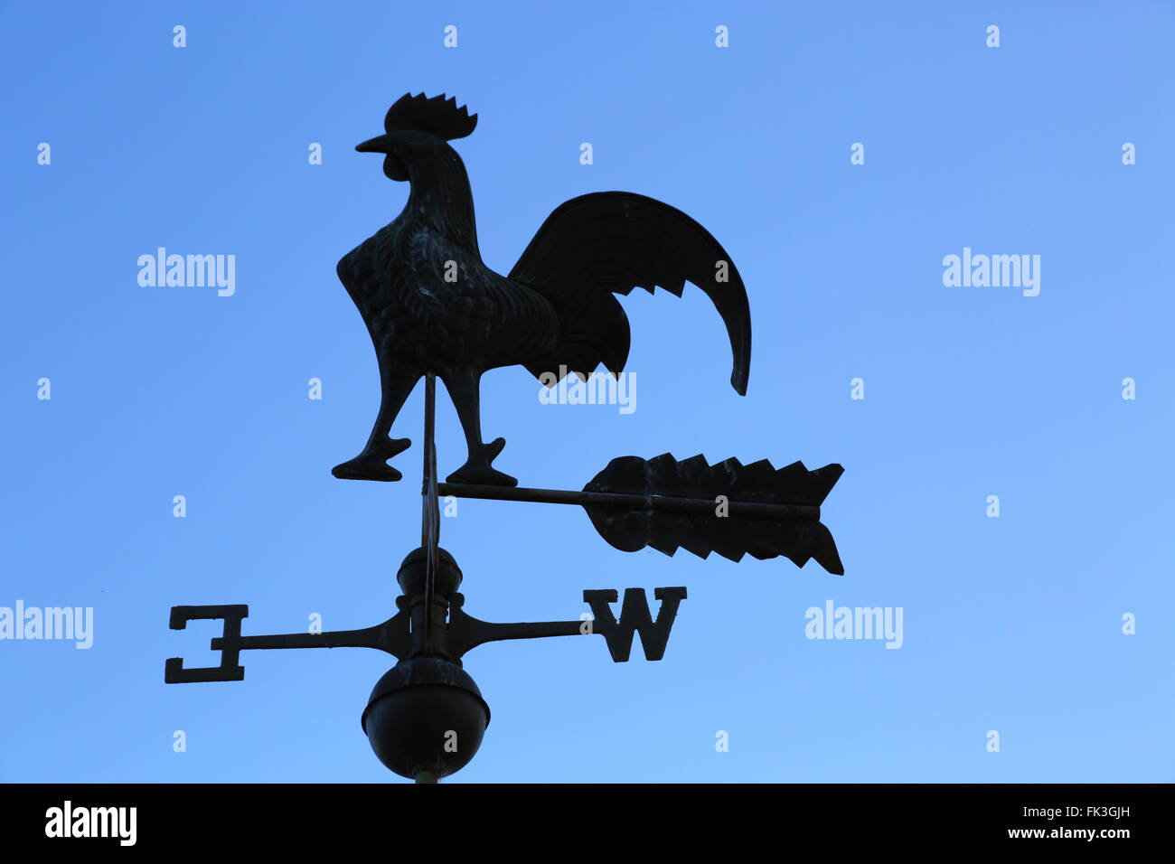 A rooster wind vane silhouetted in front of a blue sky. - Stock Image