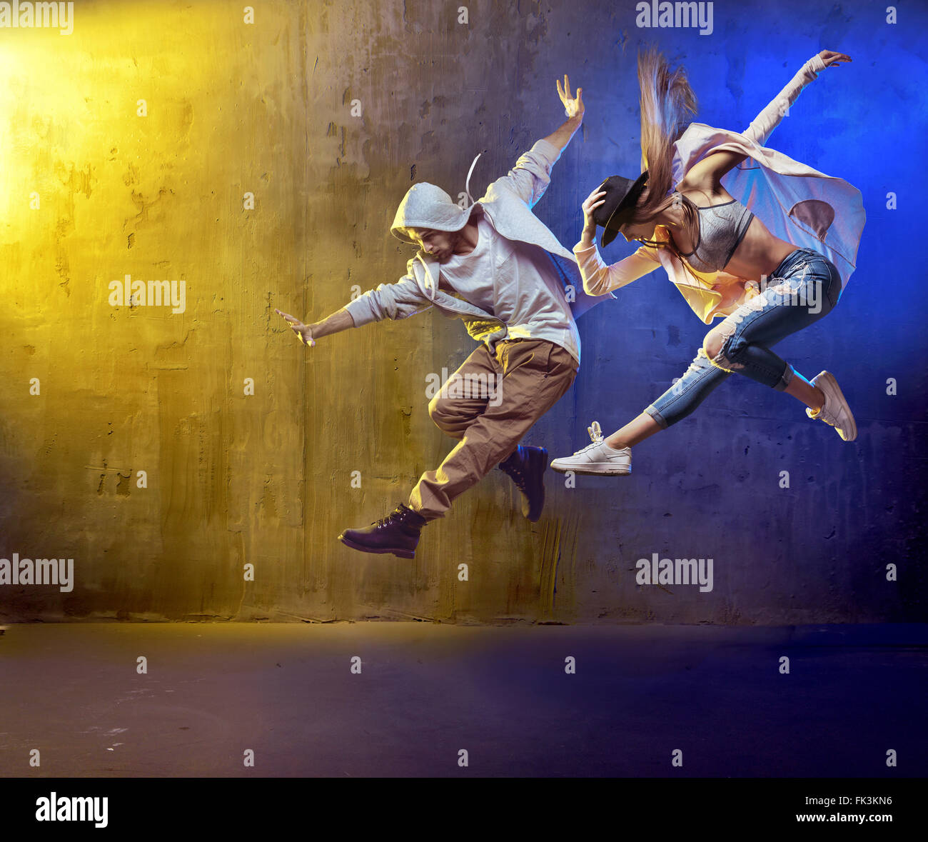 Stylish dancers dancing in a concrete place - Stock Image