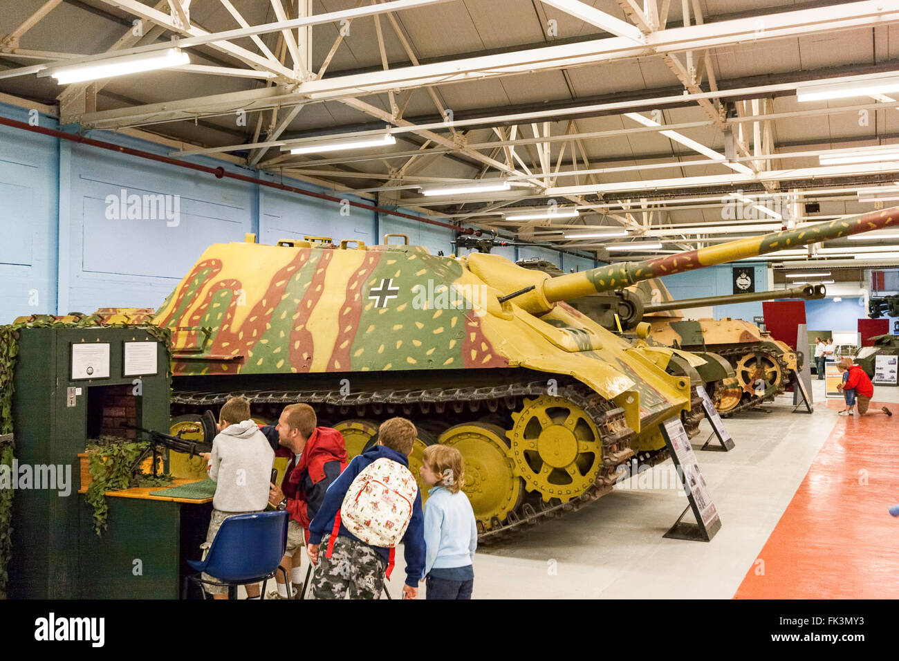 Bovington tank museum interior display. Row of German tanks with Jagpanther tank and father and three children looking - Stock Image