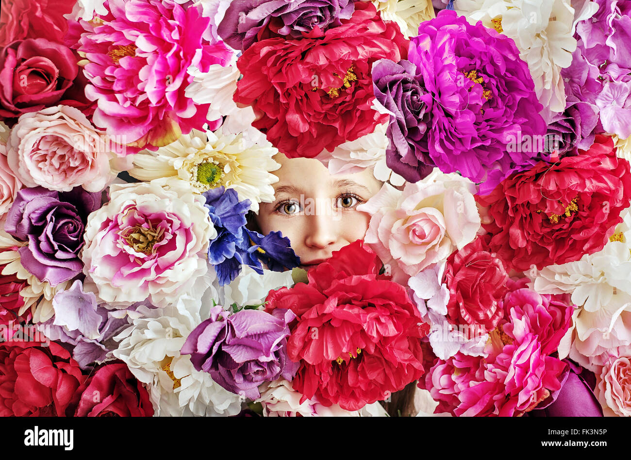 Conceptual picture of little girl behind a flower wall - Stock Image