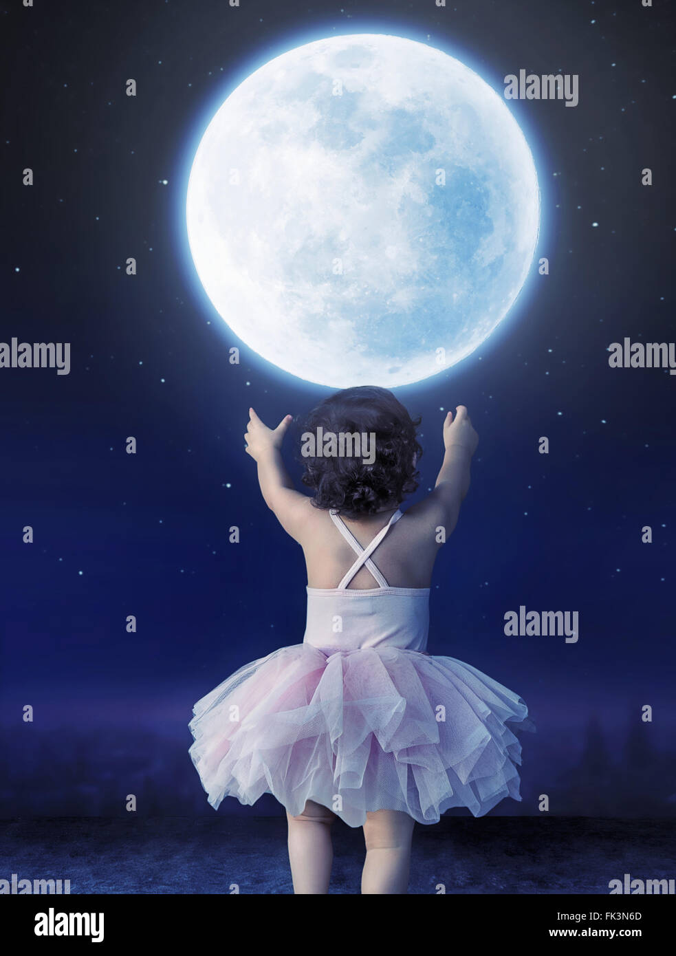 Cute baby girl reaching to the moon - Stock Image