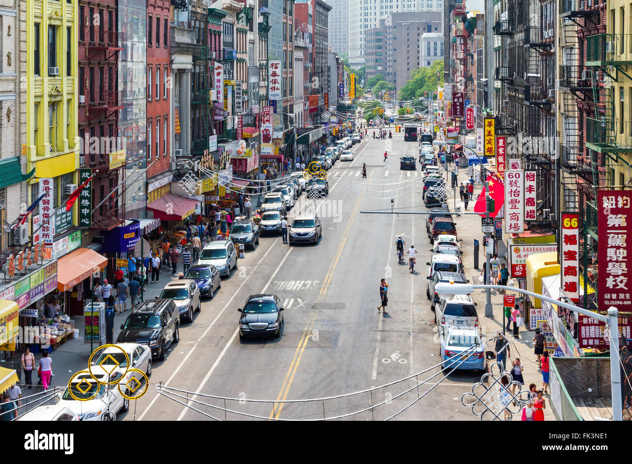 NEW YORK CITY - JULY 2015: Tourists shop at businesses along a busy street in historic Chinatown during 4th of July Stock Photo
