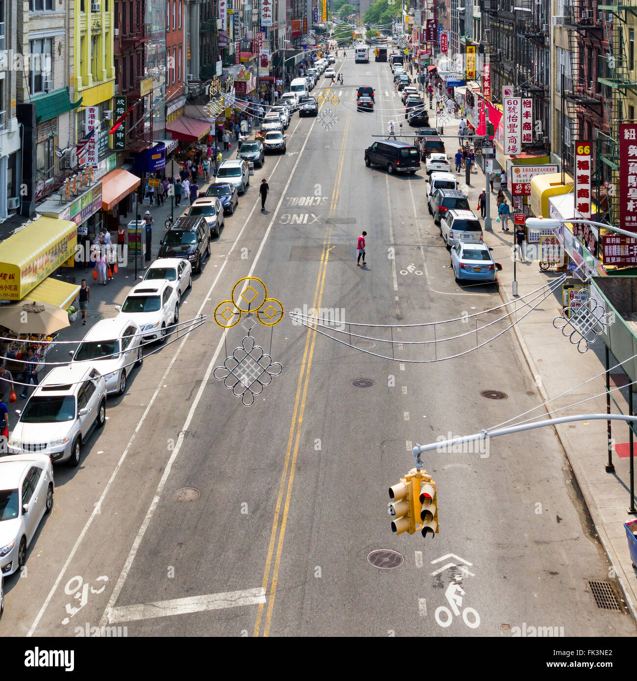 NEW YORK CITY - JULY 2015: People shop at stores along a busy block in the Chinatown neighborhood of Manhattan during Stock Photo