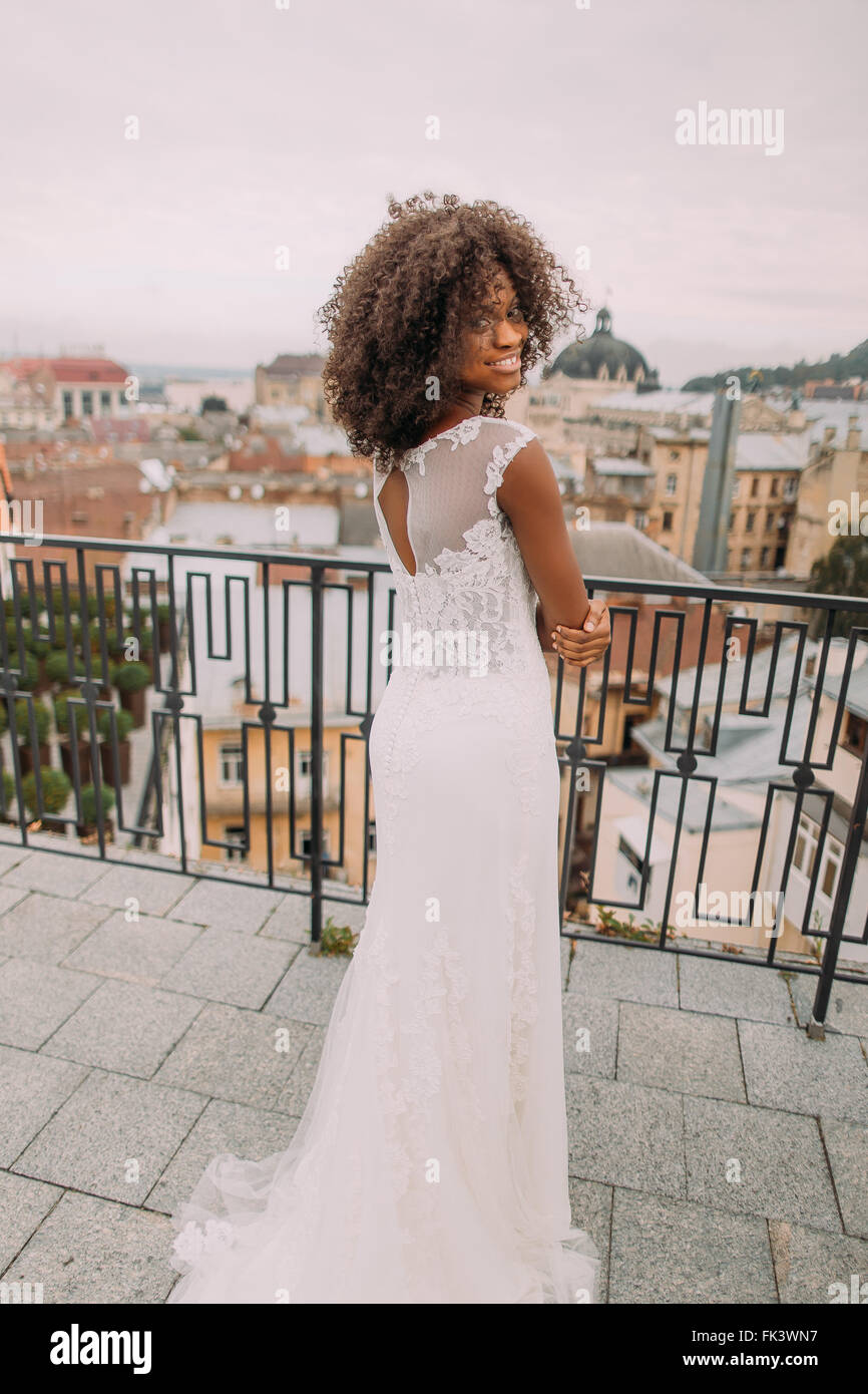 Pretty african bride in vintage lace dress posing for camera on the terrace - Stock Image