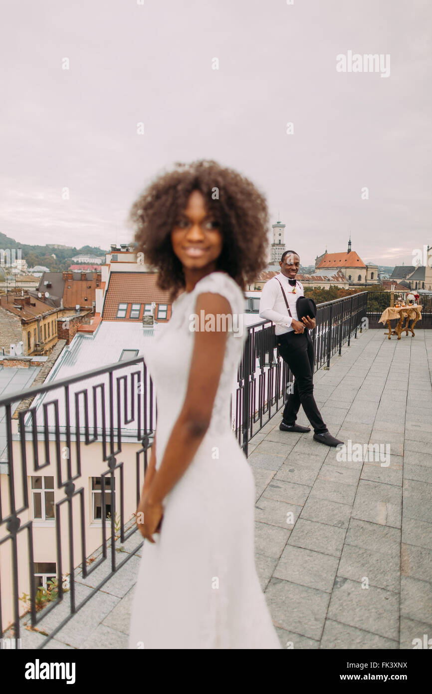 Happy wedding couple smoling on the terrace. Wedding day - Stock Image