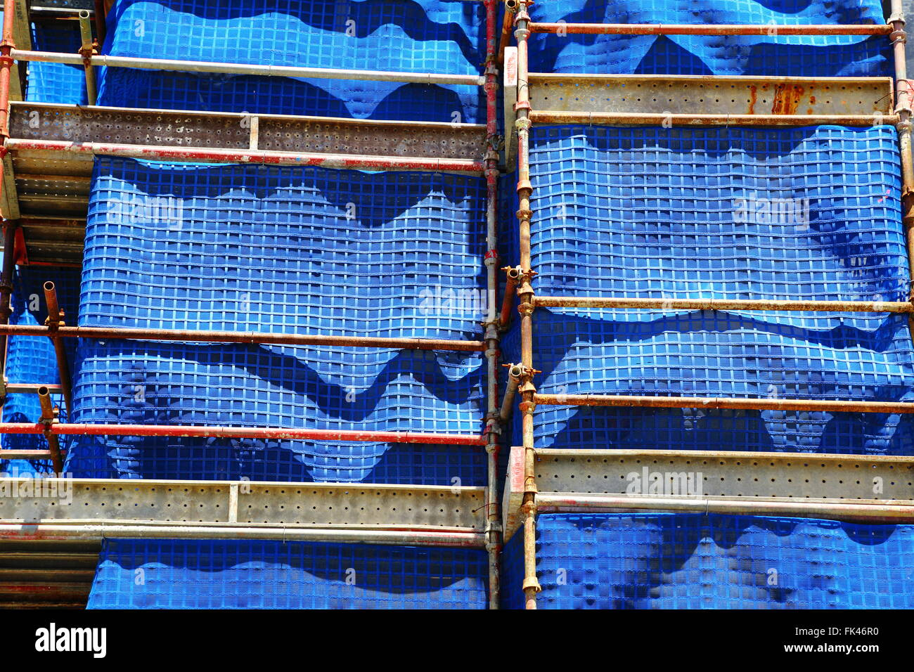 Building construction scaffolding with blue fabric. - Stock Image