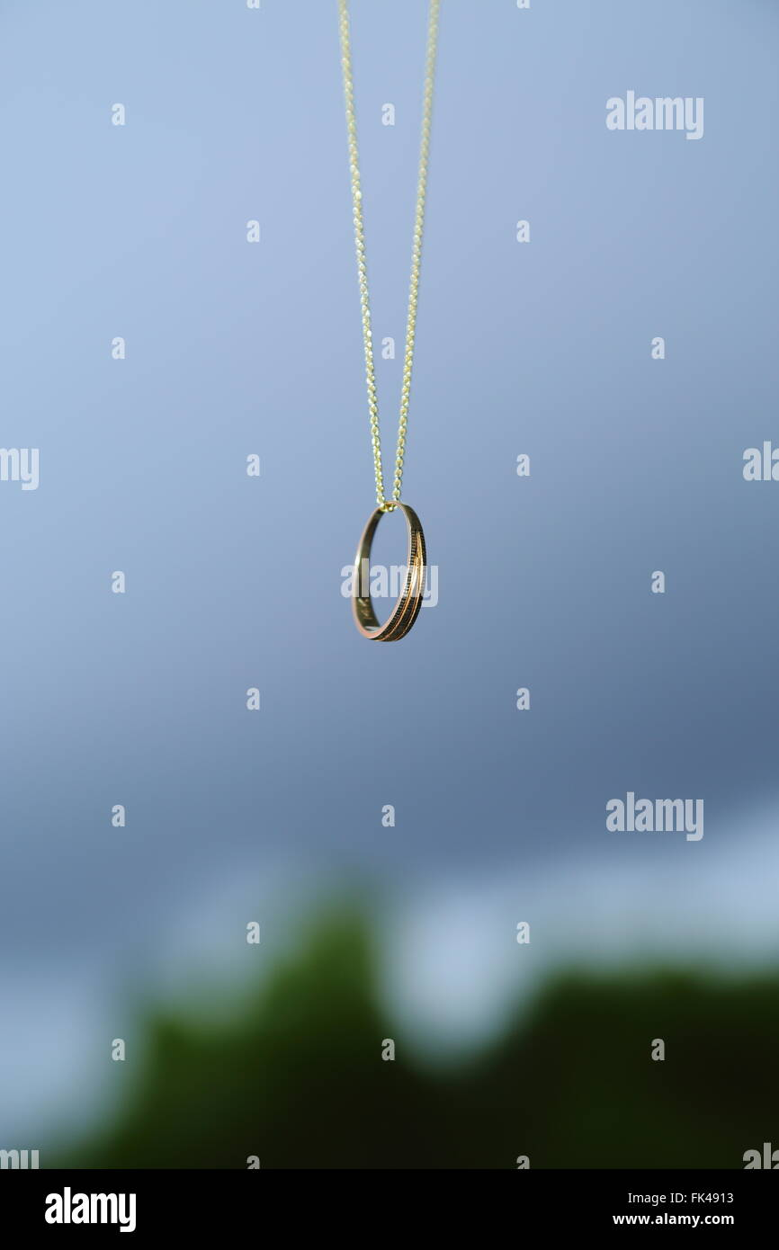 A wedding ring dangling on a chain. - Stock Image