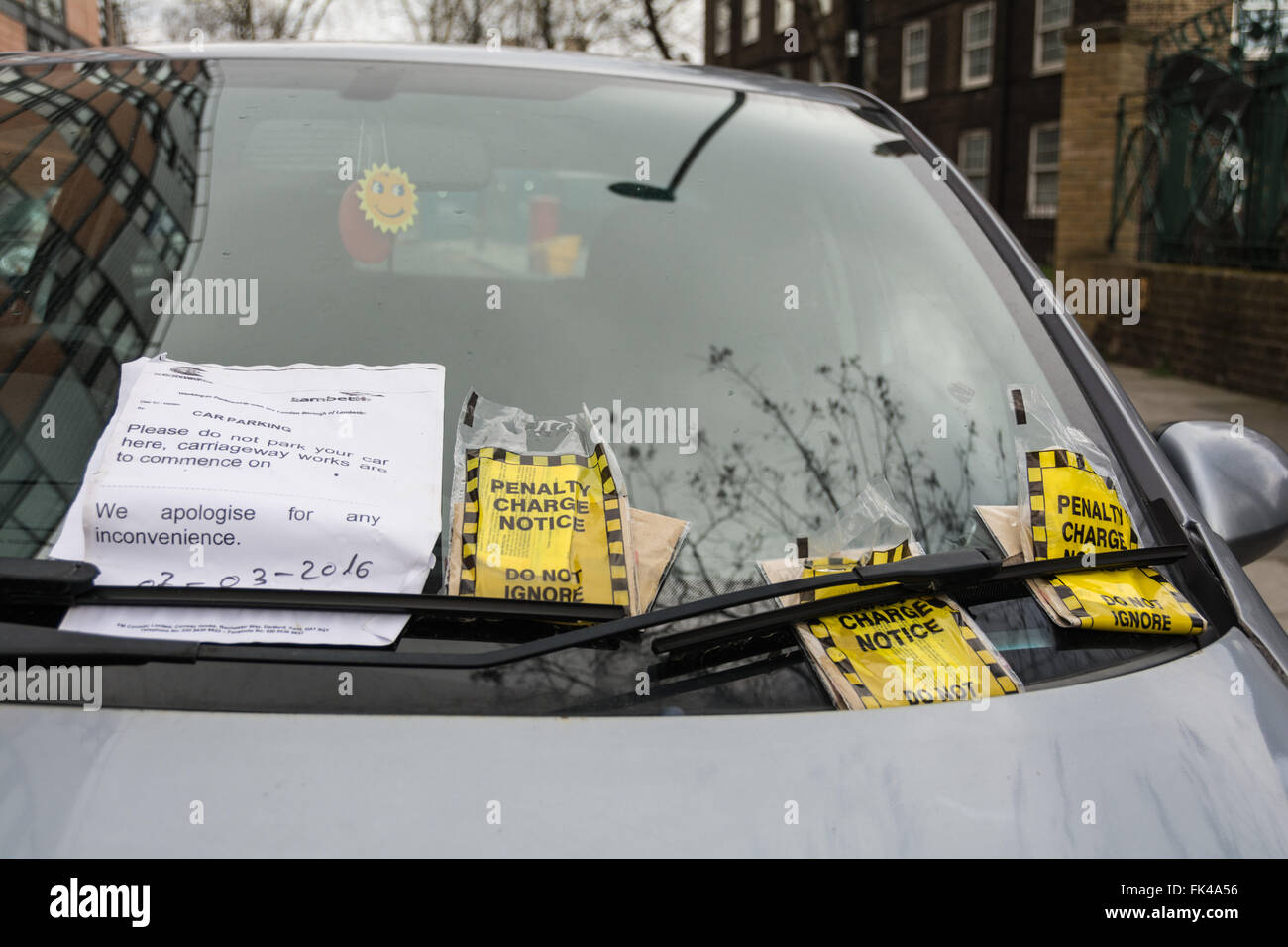 Three penalty charge notice tickets on a car windscreen in London, England, UK - Stock Image