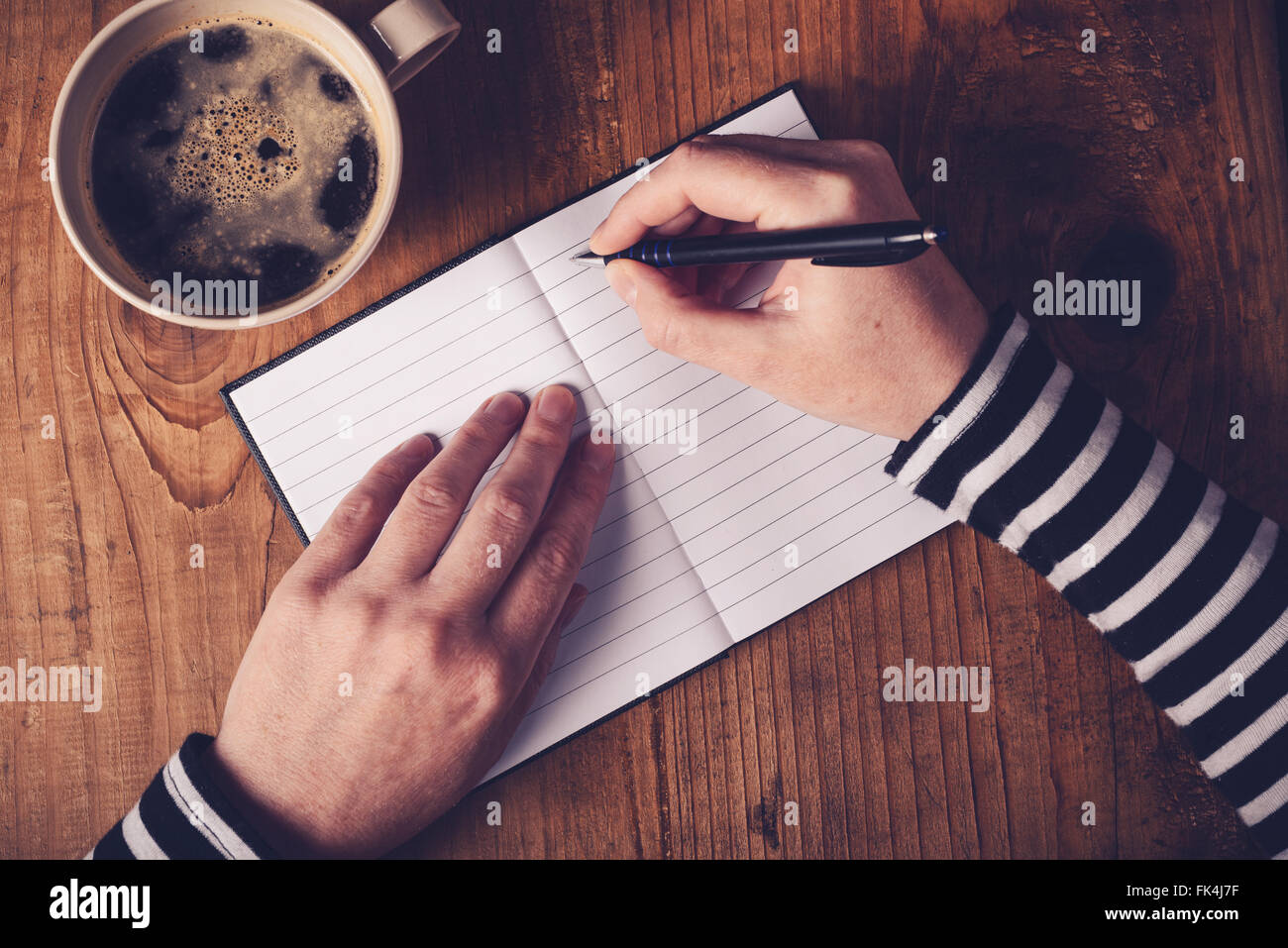 Woman drinking coffee and making a diary note, top view of female hands writing in notebook, retro toned image - Stock Image