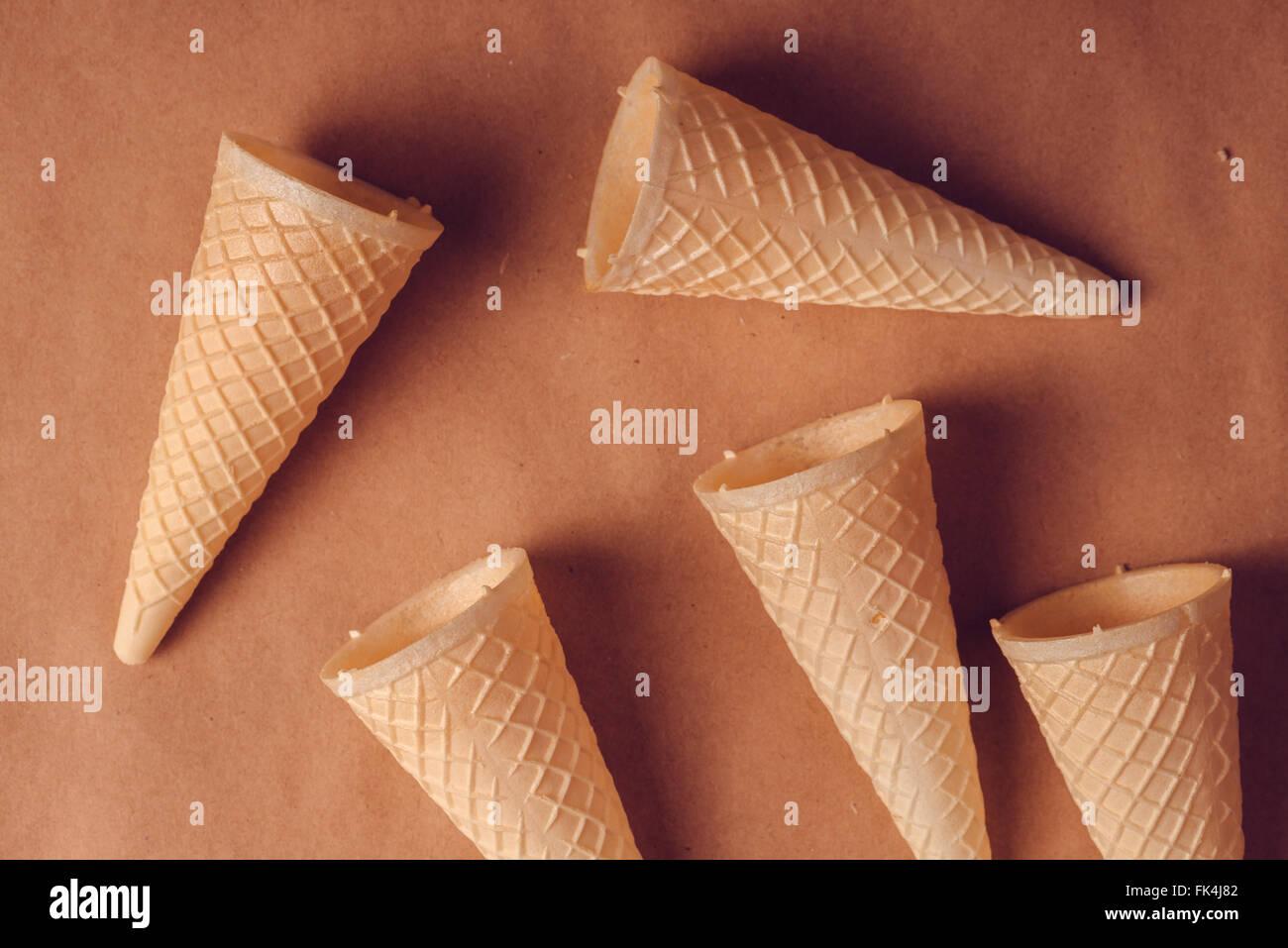 Scaterred crispy ice cream cone stack, warm retro tone, soft light, top view - Stock Image