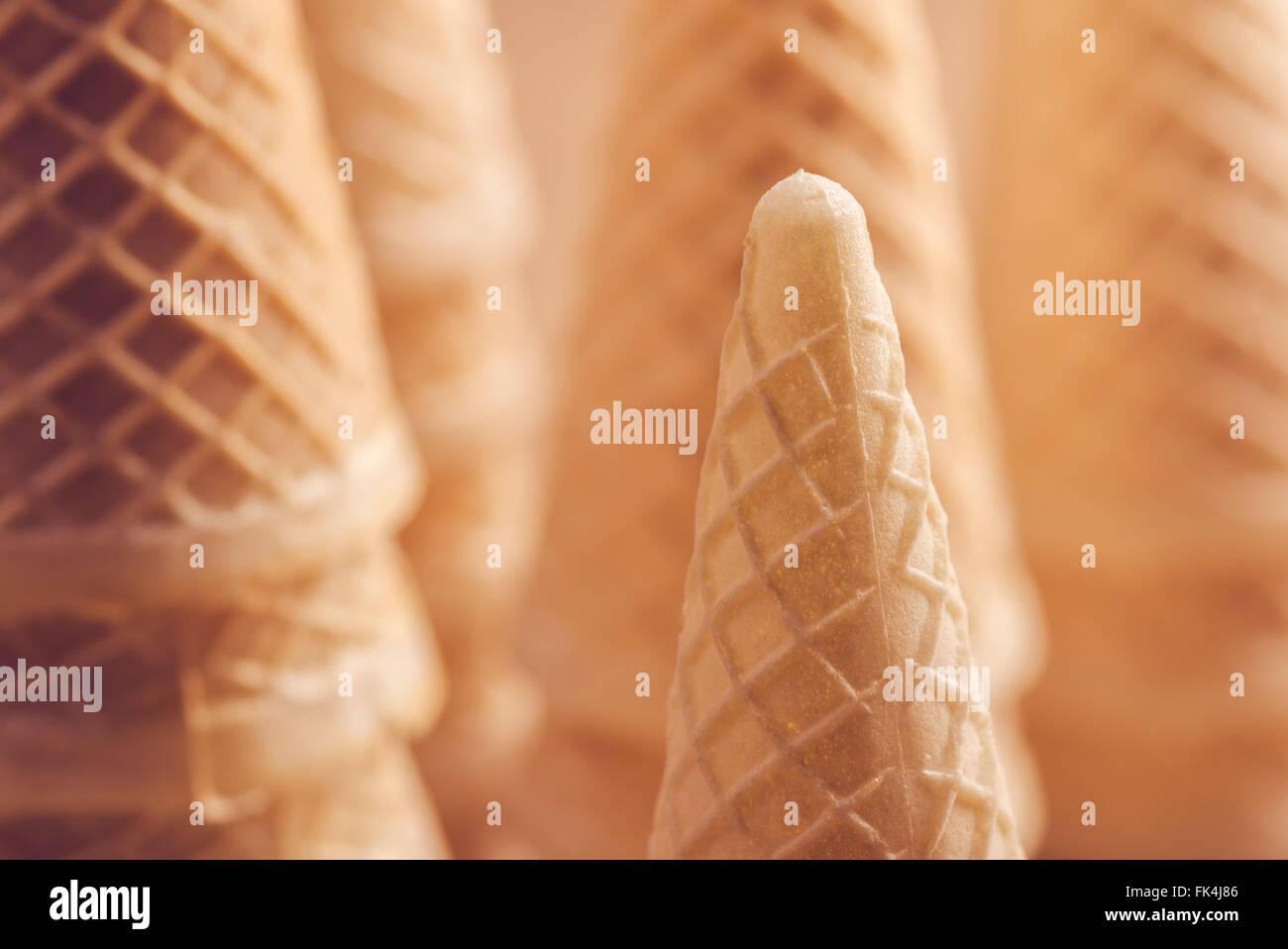 Crispy ice cream cone stack macro detail, warm retro tone, soft light - Stock Image