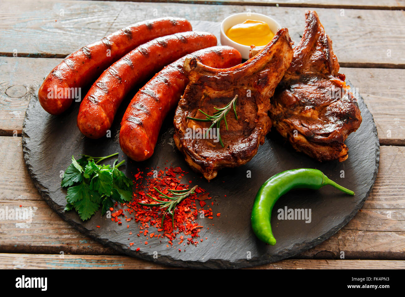 Grilled sausages and steak on the bone barbecue - Stock Image