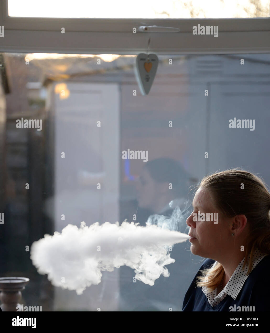 Young woman vaping in a conservatory and reflections in glass. - Stock Image