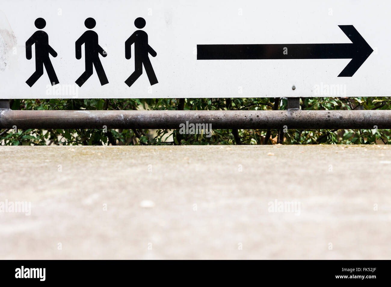 pictogram, silhouettes of three persons following an arrow - Stock Image