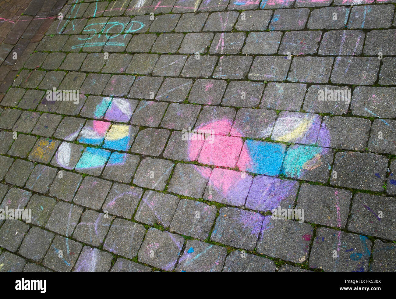 colored chalk drawing showing two hearts and the word stop - Stock Image
